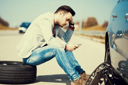 Man met autopech in het midden van de straat, na auto-breakdown.He aan de telefoon, belt voor hulp.