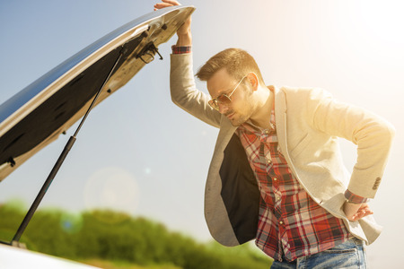 A young man with a silver car that broke down on the road. Stock Photo