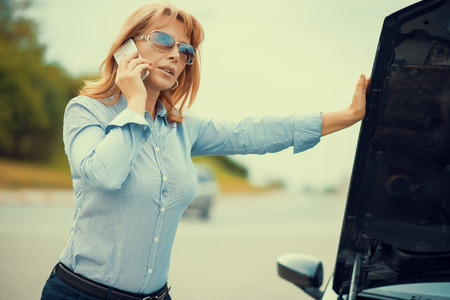 car trouble: Woman with car trouble in the middle of the street, after car breakdown.She is waiting for the technician to arrive. Stock Photo
