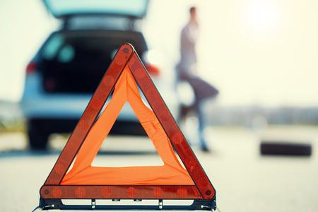 Молодой человек с серебряной автомобиль, который сломался на road.He настроил предупреждение triangle.He ждет техник, чтобы прибыть.
