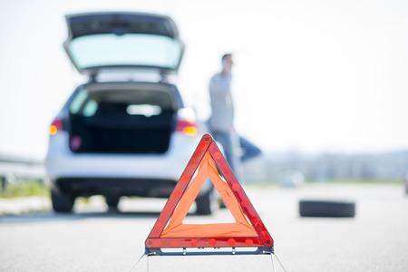 Een jonge man met een zilveren auto die kapot ging op de weg. Hij heeft een gevarendriehoek opgesteld. Hij wacht tot de technicus arriveert.
