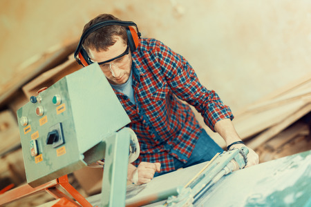 machine teeth: Close up of a young carpenter at work.He is using a bandsaw, also known as a jigsaw or a scroll saw, cuts through a piece of wood.