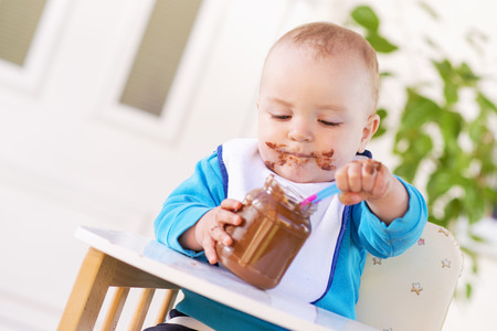 smeared baby: A baby grabbing a jar of chocolate cream while sitting in his high chair.His face and hands smeared with chocolate cream.