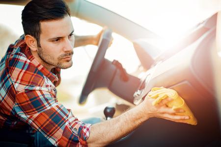 Jonge mens die zijn auto in openlucht schoonmaakt. Mens die het binnenland van zijn auto schoonmaakt.