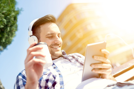 handsfree device: Close up of a young man sitting outdoors listening to music.He is drinking coffee to go.