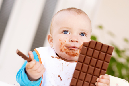 smeared baby: Baby boy eating chocolate.His face and hands smeared with chocolate. Stock Photo