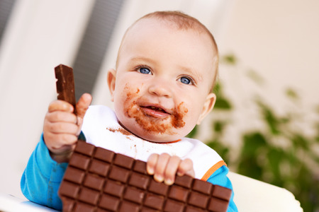 Baby boy eating chocolate.His face and hands smeared with chocolate. Stock Photo