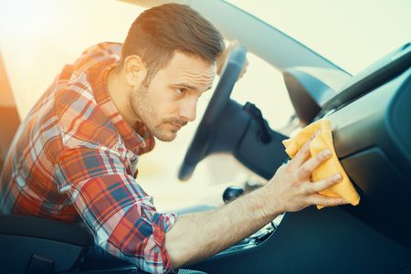 Young man cleaning his car outdoors.Man cleaning the dashboard of his car. Banco de Imagens