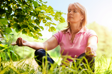 Middle aged woman doing yoga meditation outdoors.