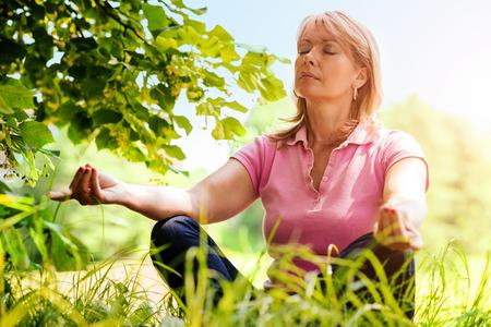 Midden oude vrouw doet yoga meditatie buitenshuis.