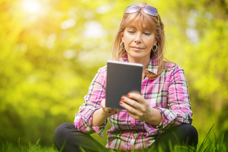 Beautiful mature woman in the park using a digital tablet.
