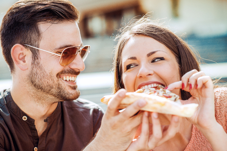 italian ethnicity: Couple eating pizza snack outdoors.They are sharing pizza and eating. Stock Photo