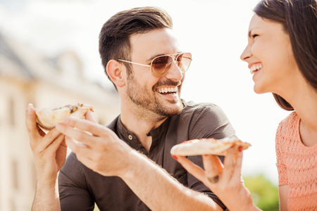 italian ethnicity: Couple eating pizza,having a great time. Stock Photo