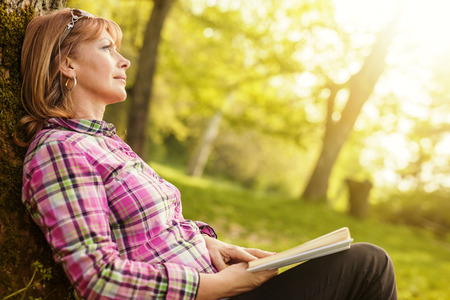 one mature woman only: Happy woman reading a book during springtime in nature
