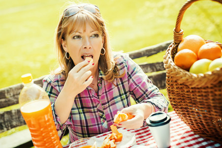 mid adult: Portrait of a smiling mid adult lady enjoying in fruit on a picnic