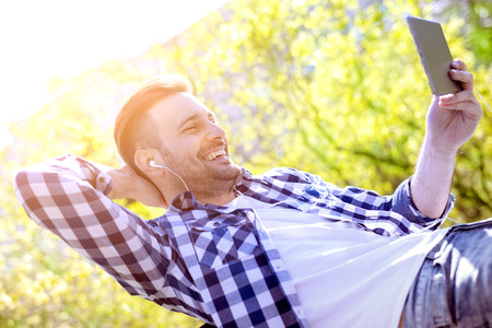 handsfree device: Young man sitting outdoors listening to music.He is sitting in the park.