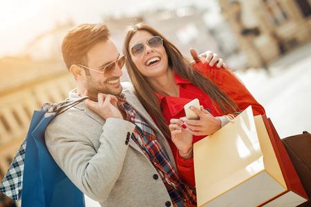 Vrolijk paar winkelen samen in de city.Couple toeristen lopen in een stad straat. Stockfoto