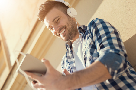 handsfree device: Close up of a young man sitting outdoors listening to music.He is enjoying the music.