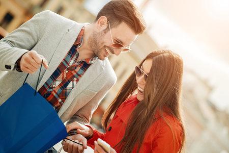 Cheerful couple shopping together in the city.They are enjoying in shopping together. Banco de Imagens