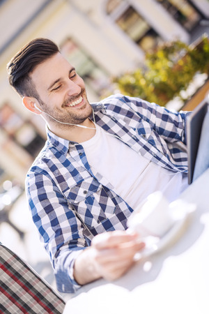 handsfree device: Handsome young man drinking coffee and looking at his smart phone