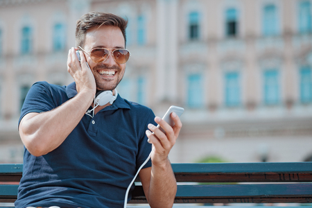 mp3 player: Close up of handsome young  man smiling while listening to music.