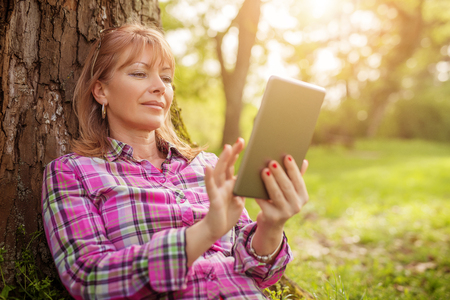 Beautiful mature woman in the park using a digital tablet