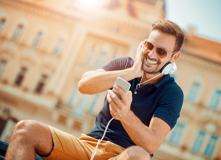 mp3 player: Young man listening to music on a smart phone.He is listening music on smartphone in the city.