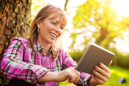 Beautiful mature woman in the park using a digital tablet.Relaxing in nature.