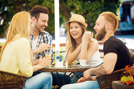 personas comunicandose: Grupo de jóvenes alegres que se comunican y se divierten en el bar. Foto de archivo
