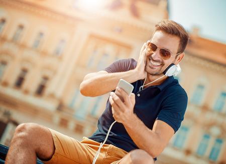 Jonge mens die aan muziek op een slimme telefoon luistert. Hij is het luisteren muziek op smartphone in de stad. Stockfoto