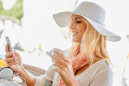 Woman using her mobile phone and holding cup of coffee at the coffee shop.