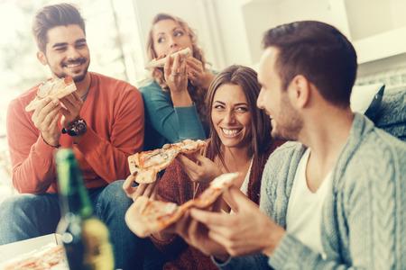 Vrienden die pizza.They hebben feestje thuis, het eten van pizza en plezier.