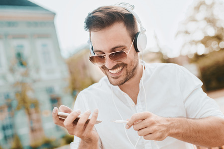 hands free phone: Young attractive man is smiling while wearing headphones. Stock Photo