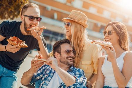 Primer plano de cuatro jóvenes alegres que comen pizza.Group de amigos que tienen sus porciones de pizza.