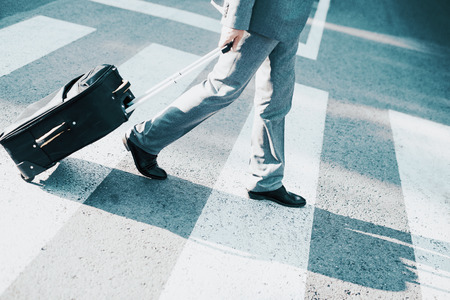 jetsetter: Close up of businessman carrying suitcase while walking on zebra crossing. Stock Photo