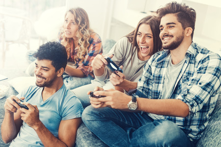 Opgewonden vrienden die thuis videogames spelen en plezier hebben. Stockfoto
