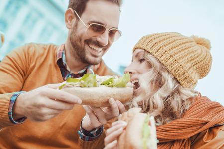 Gelukkig jong couple.They lachen en het eten van sandwich en een geweldige tijd. Stockfoto