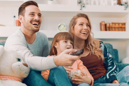 Young family watching TV together at home and having fun together. Banque d'images