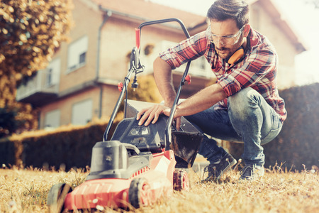 Man cutting grass in his yard with lawn mower. Banque d'images