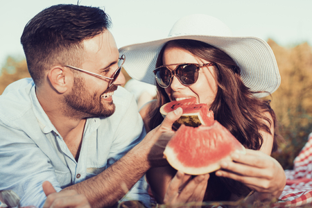 Young couple on a picnic together bite a one piece of watermelon. Reklamní fotografie