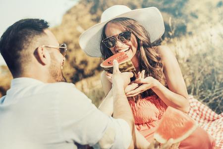Pareja feliz en una sandía de picnic comiendo en un día soleado. Foto de archivo