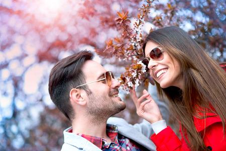 caída pareja feliz en el amor bajo un cerezo hermoso.