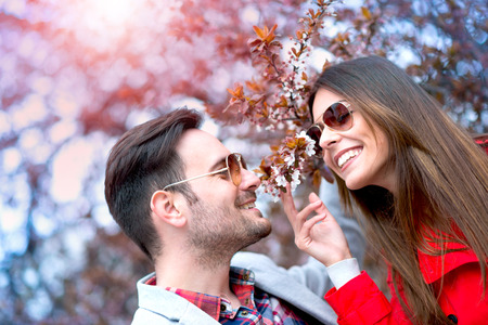 Happy couple fall in love under a beautiful cherry tree. Stock Photo