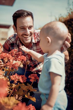 父と息子が庭で一緒に作業します。植物の花に彼の父を助ける小さな男の子。