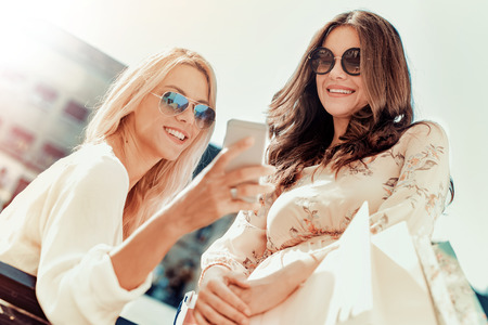 Amigos que hacen las mujeres jóvenes que hacen selfie.Two autofoto en la ciudad.
