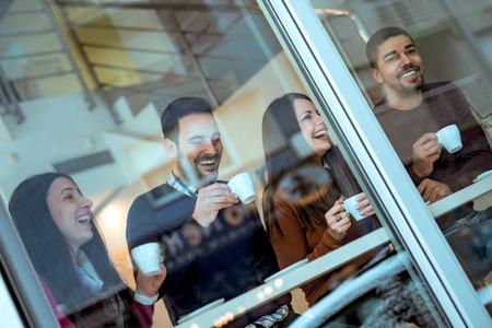 Vrienden hebben een geweldige tijd gehad in cafe.Friends lachend en zitten in een coffeeshop, koffie te drinken en samen genieten. Stockfoto - 71325535