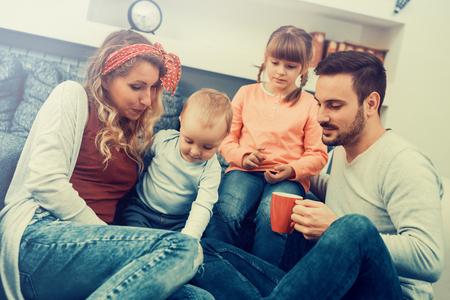 Feliz madre, padre e hijos en el hogar.