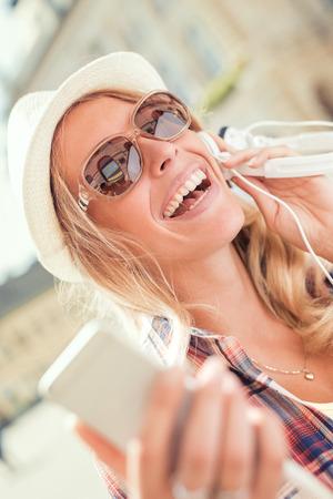 Jeune femme écoutant de la musique sur un téléphone intelligent à l'extérieur. Banque d'images - 71325471