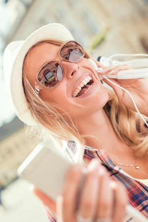 Young woman listening to music on a smart phone outdoors. Stock Photo