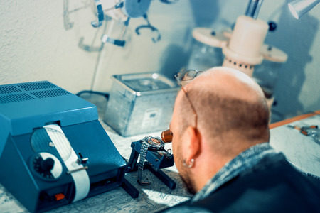 Close up portrait of a watchmaker at work.A watchmaker or repair man in action,viewing very closely a swiss watch. Stock Photo